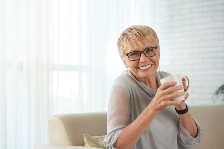 Older woman with short blonde hair holding a mug and smiling while sitting on a couch in a living room setting.