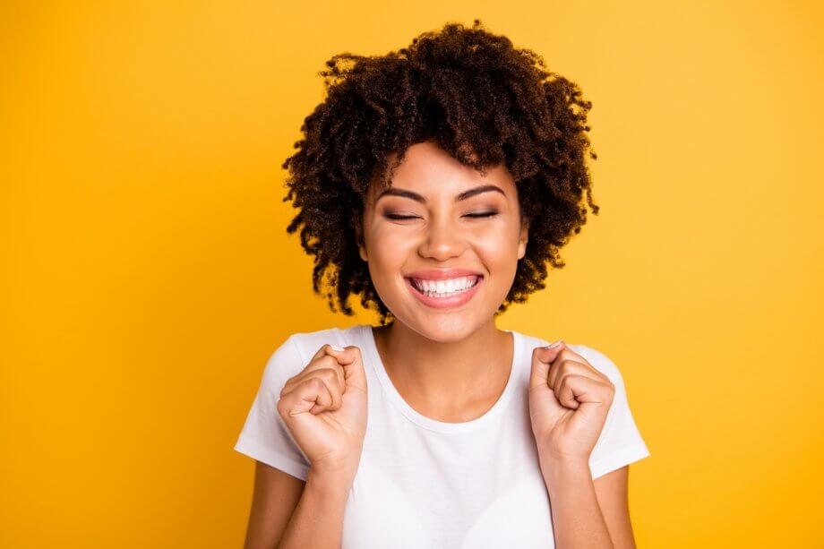 Photograph of a woman with short curly hair smiling in an excited way standing in front of a bright yellow/orange background.